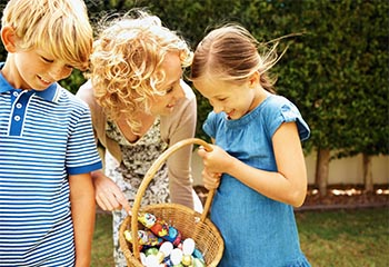 Mother holding Easter basket full of Easter eggs with her son and daughter
