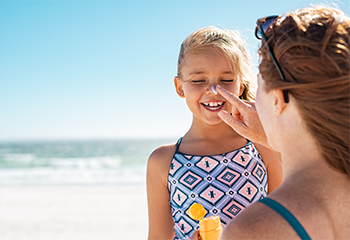 Mother applied sunscreen to young girl's face on the beach