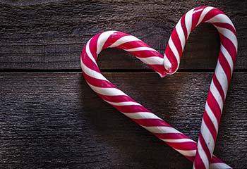 Two candy canes positioned in a heart shape on dark wooden background